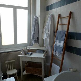 Immagine di una stanza da bagno padronale scandinava di medie dimensioni con vasca da incasso, vasca/doccia, piastrelle blu, piastrelle in ceramica, pareti bianche, pavimento alla veneziana e lavabo a consolle