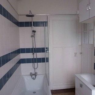 Foto di una stanza da bagno padronale nordica di medie dimensioni con vasca da incasso, vasca/doccia, piastrelle blu, piastrelle in ceramica, pareti bianche, pavimento alla veneziana e lavabo a consolle