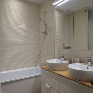 Ispirazione per una stanza da bagno padronale minimal di medie dimensioni con vasca sottopiano, piastrelle beige, piastrelle in ceramica, pareti bianche, pavimento in linoleum, lavabo da incasso e top in legno