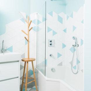 Idées déco pour une salle de bain principale contemporaine de taille moyenne avec un placard à porte affleurante, des portes de placard noires, un combiné douche/baignoire, un carrelage multicolore, des carreaux de béton, béton au sol, un plan vasque, un sol gris, une baignoire d'angle, un WC séparé, un mur bleu, une cabine de douche à porte battante, un plan de toilette blanc et meuble simple vasque.