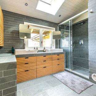 Immagine di una stanza da bagno padronale nordica di medie dimensioni con ante in legno chiaro, vasca sottopiano, WC sospeso, piastrelle grigie, piastrelle in ardesia, pareti grigie, pavimento in ardesia, lavabo da incasso, pavimento grigio, porta doccia scorrevole e top multicolore