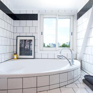 Aménagement d'une salle de bain principale classique avec une baignoire encastrée, un carrelage blanc, un carrelage noir, un mur blanc et un sol en bois brun.