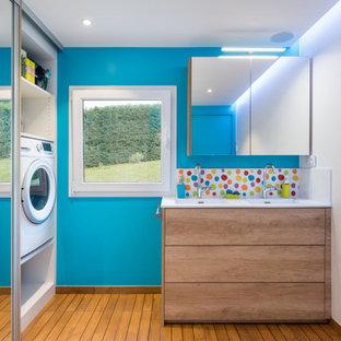 Cette photo montre une salle d'eau tendance de taille moyenne avec un placard à porte plane, des portes de placard en bois brun, un mur bleu, un lavabo intégré, un sol marron et un plan de toilette blanc.