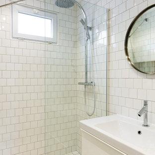 Cette image montre une salle d'eau nordique de taille moyenne avec des portes de placard blanches, un carrelage blanc, un placard à porte plane, une douche à l'italienne, des carreaux de porcelaine, un mur blanc, un sol en carrelage de porcelaine, un plan vasque, un plan de toilette en surface solide, un sol blanc, une cabine de douche à porte battante et un plan de toilette blanc.