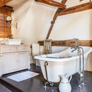Exemple d'une salle de bain principale nature de taille moyenne avec un placard en trompe-l'oeil, des portes de placard beiges, une baignoire sur pieds, un mur blanc, une vasque et un WC séparé.