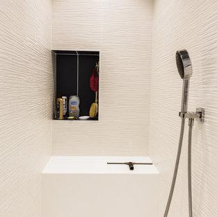 Modelo de cuarto de baño principal, moderno, de tamaño medio, con armarios con rebordes decorativos, puertas de armario azules, ducha a ras de suelo, sanitario de pared, baldosas y/o azulejos blancos, baldosas y/o azulejos de cerámica, paredes blancas, suelo de madera pintada, lavabo tipo consola, encimera de acrílico, suelo gris y ducha abierta