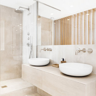 Idéer för att renovera ett mellanstort funkis en-suite badrum, med en kantlös dusch, en toalettstol med separat cisternkåpa, beige kakel, vit kakel, beige väggar, travertin golv, ett fristående handfat och kaklad bänkskiva
