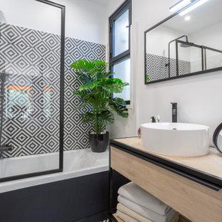 Exemple d'une petit salle de bain principale tendance avec des portes de placard en bois clair, une baignoire encastrée, un combiné douche/baignoire, un WC séparé, un carrelage noir et blanc, des carreaux de béton, un mur blanc, un sol en carreaux de ciment, un plan vasque, un plan de toilette en bois, meuble simple vasque, meuble-lavabo suspendu et une cabine de douche à porte coulissante.