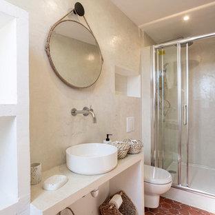 他の地域の中くらいのエクレクティックスタイルのおしゃれな浴室 (オープンシェルフ、一体型トイレ、ベージュの壁、テラコッタタイルの床、オーバーカウンターシンク、赤い床、引戸のシャワー、ベージュのカウンター) の写真