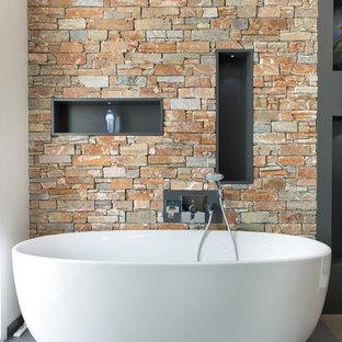 Cette image montre une salle de bain principale design avec une baignoire indépendante et un carrelage de pierre.