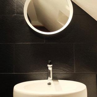 Ispirazione per una piccola stanza da bagno con doccia moderna con ante a filo, ante bianche, doccia alcova, piastrelle nere, piastrelle in ardesia, pareti nere, pavimento in laminato, lavabo da incasso, top in laminato, pavimento beige e porta doccia a battente