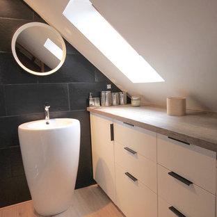 Foto di una piccola stanza da bagno con doccia moderna con ante a filo, ante bianche, doccia alcova, piastrelle nere, piastrelle in ardesia, pareti nere, pavimento in laminato, lavabo da incasso, top in laminato, pavimento beige e porta doccia a battente