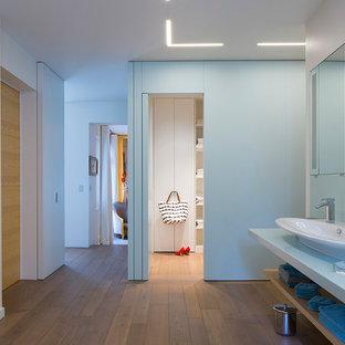 Aménagement d'une grande salle de bain principale contemporaine avec un sol en bois brun, une grande vasque, un sol marron, un placard sans porte et un mur blanc.