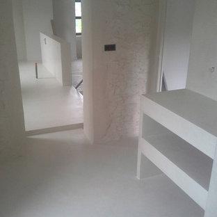 Immagine di una stanza da bagno con doccia country con doccia a filo pavimento, pareti bianche, pavimento in cemento e top in cemento