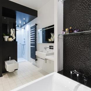 Cette image montre une grand douche en alcôve principale traditionnelle avec une baignoire posée, un bidet, un carrelage noir, un mur blanc et un lavabo suspendu.