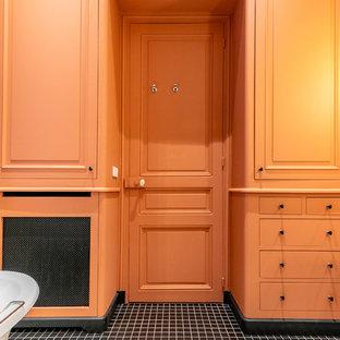 Klassisk inredning av ett mellanstort vit vitt en-suite badrum, med luckor med profilerade fronter, orange skåp, ett badkar med tassar, en dusch i en alkov, vit kakel, tunnelbanekakel, orange väggar, cementgolv, ett konsol handfat, bänkskiva i akrylsten, svart golv och dusch med gångjärnsdörr