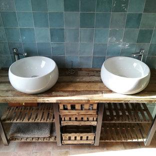 Стильный дизайн: большая главная ванная комната в стиле лофт с открытыми фасадами, искусственно-состаренными фасадами, зеленой плиткой, терракотовой плиткой, зелеными стенами, полом из терракотовой плитки, накладной раковиной, столешницей из дерева, коричневым полом, разноцветной столешницей, тумбой под две раковины и подвесной тумбой - последний тренд