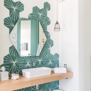 Imagen de cuarto de baño mediterráneo con baldosas y/o azulejos verdes, paredes blancas, lavabo sobreencimera, encimera de madera y suelo gris