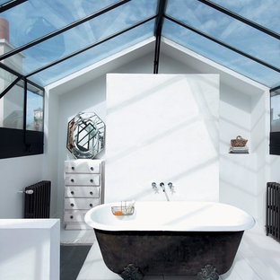 Design ideas for a mid-sized eclectic master bathroom in Grenoble with distressed cabinets, a claw-foot tub, white walls and painted wood floors.