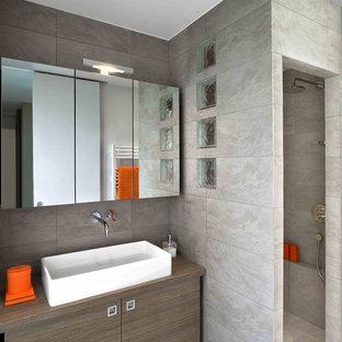 Idée de décoration pour une salle de bain design de taille moyenne avec des portes de placard en bois brun, un carrelage gris, un plan de toilette en bois, aucune cabine et un plan de toilette marron.