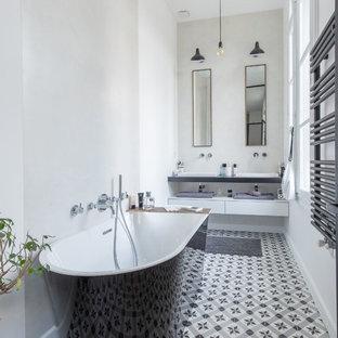 Idée de décoration pour une salle de bain design avec une baignoire indépendante, un mur gris, une vasque et un sol multicolore.