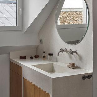 Cette photo montre une salle de bain scandinave avec un placard à porte plane, des portes de placard en bois clair, un mur blanc, un lavabo intégré, un sol multicolore et un plan de toilette blanc.