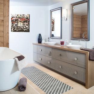 Exemple d'une douche en alcôve principale tendance de taille moyenne avec une baignoire indépendante, un mur blanc, un sol en bois clair, une vasque, un plan de toilette en bois, des portes de placard marrons et un plan de toilette marron.