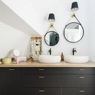 Idée de décoration pour une salle d'eau design avec un placard à porte plane, des portes de placard noires, un mur blanc, une vasque et un plan de toilette en bois.