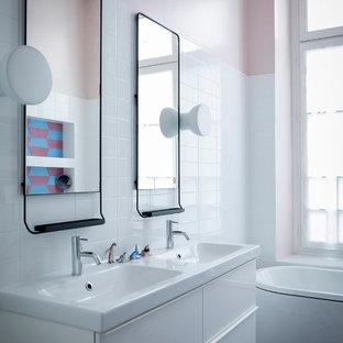 Idées déco pour une salle de bain contemporaine avec un placard à porte plane, des portes de placard blanches, une baignoire indépendante, un carrelage blanc, un mur rose, un plan vasque et un sol multicolore.