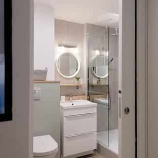 Cette image montre une salle de bain design avec un placard à porte plane, des portes de placard blanches, un WC suspendu, un carrelage gris, un mur blanc, un sol en bois clair, un plan vasque, un sol beige et aucune cabine.