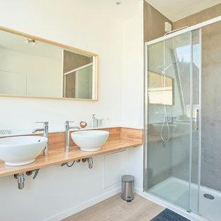 Immagine di una stanza da bagno padronale contemporanea di medie dimensioni con ante bianche, doccia a filo pavimento, piastrelle bianche, pareti bianche, parquet chiaro, lavabo rettangolare, top in legno, pavimento marrone e porta doccia scorrevole