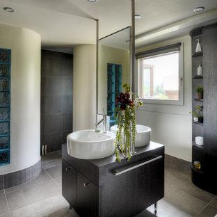 Exemple d'une salle de bain principale tendance de taille moyenne avec un placard à porte plane, des portes de placard en bois sombre, un carrelage gris, un mur blanc et une vasque.
