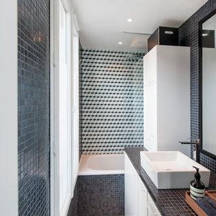 Réalisation d'une salle de bain design avec un placard à porte plane, des portes de placard blanches, une baignoire posée, un combiné douche/baignoire, un carrelage multicolore, une vasque, un plan de toilette en carrelage, un sol beige et un plan de toilette noir.