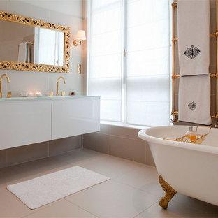 Cette image montre une très grand salle de bain principale traditionnelle avec une baignoire sur pieds, un plan de toilette en verre et un mur beige.