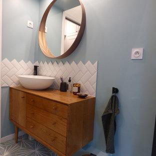 Esempio di una piccola stanza da bagno con doccia minimalista con vasca da incasso, doccia alcova, WC sospeso, piastrelle bianche, piastrelle in ceramica, pareti blu, pavimento con piastrelle in ceramica, lavabo da incasso, top in legno, pavimento blu, porta doccia scorrevole e top beige