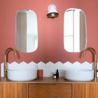 Réalisation d'une salle de bain ethnique avec un placard en trompe-l'oeil, des portes de placard en bois brun, un mur rose, une vasque, un plan de toilette en bois et un carrelage blanc.