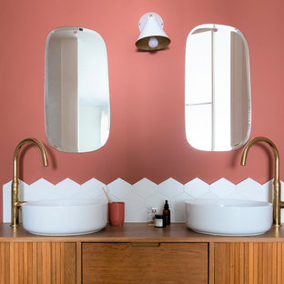 Imagen de cuarto de baño tropical con armarios tipo mueble, puertas de armario de madera oscura, paredes rosas, lavabo sobreencimera, encimera de madera y baldosas y/o azulejos blancos