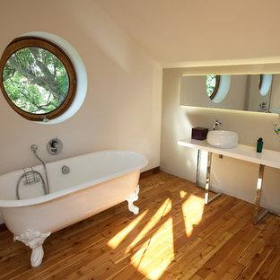 Aménagement d'une grand salle de bain éclectique avec un mur blanc, un sol en bois brun, un sol marron, une baignoire sur pieds, un combiné douche/baignoire, un lavabo posé, aucune cabine et un plan de toilette blanc.