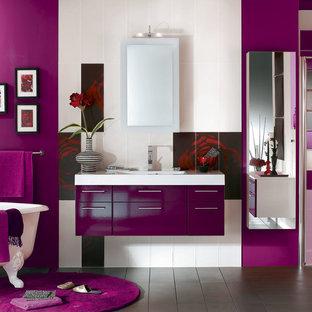 Diseño de cuarto de baño con ducha, moderno, de tamaño medio, con bañera con patas, ducha a ras de suelo, sanitario de pared, baldosas y/o azulejos grises, baldosas y/o azulejos de cerámica, paredes púrpuras, suelo de baldosas de cerámica, lavabo tipo consola y encimera de ónix