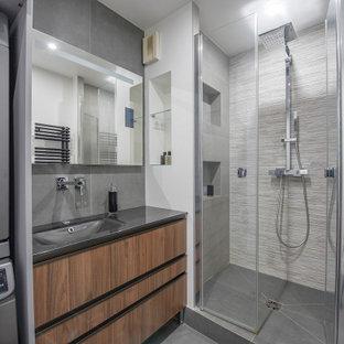 Cette photo montre une salle de bain tendance de taille moyenne avec des portes de placard en bois brun, un carrelage gris, un sol en carrelage de céramique, un plan de toilette en verre, un plan de toilette gris, une niche, un placard à porte plane, un mur blanc, un lavabo encastré, un sol gris, une cabine de douche à porte battante, meuble simple vasque et meuble-lavabo sur pied.