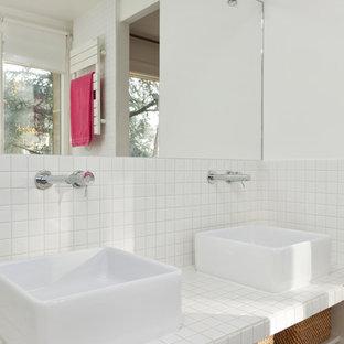 Cette photo montre une salle de bain tendance de taille moyenne avec un mur blanc, un sol en bois foncé, une vasque, un plan de toilette en carrelage, un carrelage blanc, un placard sans porte et des portes de placard blanches.
