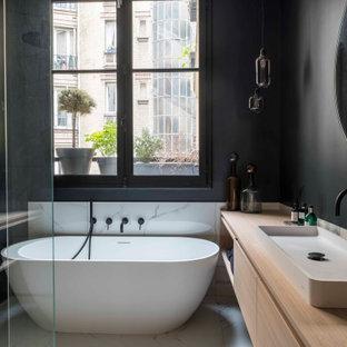 Cette image montre une grand salle de bain principale design avec un placard à porte plane, des portes de placard en bois clair, une baignoire indépendante, une douche d'angle, un mur noir, un sol en carrelage de céramique, un plan vasque, un plan de toilette en bois, un sol gris, aucune cabine et un plan de toilette marron.