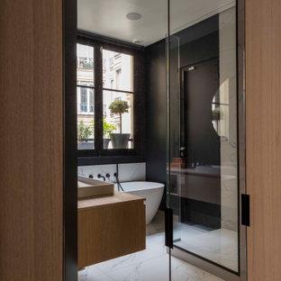 パリの広いコンテンポラリースタイルのおしゃれなマスターバスルーム (フラットパネル扉のキャビネット、淡色木目調キャビネット、置き型浴槽、黒い壁、セラミックタイルの床、コンソール型シンク、木製洗面台、グレーの床、オープンシャワー、ブラウンの洗面カウンター、コーナー設置型シャワー) の写真