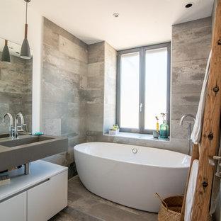 Inspiration pour une salle d'eau design avec un placard à porte plane, des portes de placard blanches, une baignoire indépendante, un carrelage gris, un mur blanc, un lavabo intégré, un sol gris et un plan de toilette gris.
