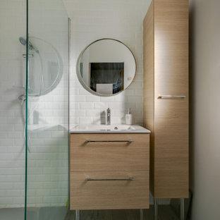 Cette image montre une salle d'eau design de taille moyenne avec une douche à l'italienne, un carrelage blanc, un carrelage métro, un mur beige, un sol marron, un placard à porte plane, des portes de placard en bois clair, un lavabo intégré et un plan de toilette blanc.