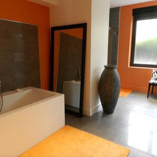 Ispirazione per una grande stanza da bagno minimal con ante bianche, vasca da incasso, doccia a filo pavimento, piastrelle grigie, piastrelle in ceramica, pareti arancioni, pavimento con piastrelle in ceramica, lavabo rettangolare, top in superficie solida e pavimento grigio