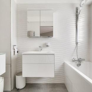 Kleines Modernes Badezimmer En Suite mit flächenbündigen Schrankfronten, weißen Schränken, Badewanne in Nische, Duschbadewanne, weißer Wandfarbe, Wandwaschbecken und offener Dusche in Paris