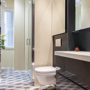 Modelo de cuarto de baño con ducha, tradicional renovado, pequeño, con armarios con paneles lisos, puertas de armario grises, ducha a ras de suelo, sanitario de pared, paredes beige, lavabo tipo consola, encimera de granito, baldosas y/o azulejos beige, baldosas y/o azulejos de metal, suelo de azulejos de cemento, suelo negro y encimeras blancas