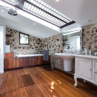 Cette image montre une salle de bain principale méditerranéenne avec un placard en trompe-l'oeil, des portes de placard blanches, un espace douche bain, un sol en bois foncé, un lavabo suspendu, un sol marron et aucune cabine.