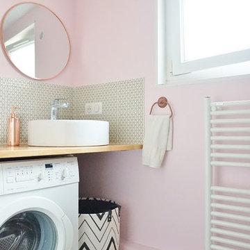Une petite salle d'eau rose et une petite cuisine grise dans un immeuble ancien